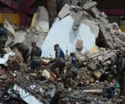 Mexican Navy members walk amid debris of the Town Hall building which